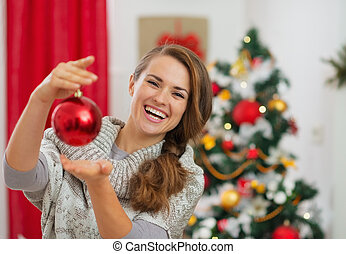 Happy young woman holding Christmas ball in front of Christmas tree