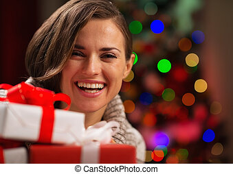 Happy young woman holding Christmas gift boxes