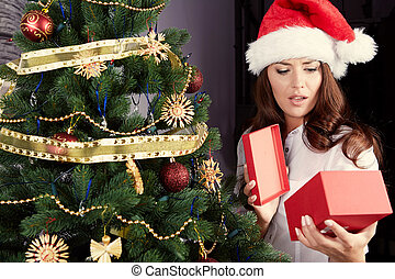 Happy young woman holding christmas present box
