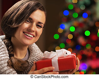 Happy young woman holding christmas present box in front of christmas lights