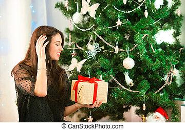 Happy young woman holding christmas present box on Christmas eve