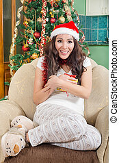 Happy young woman holding christmas present box wearing Santa hat