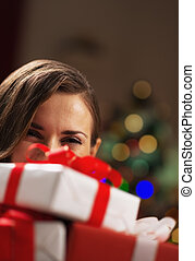 Happy young woman holding christmas present boxes in front of face