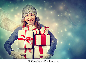 Happy young woman holding many present boxes