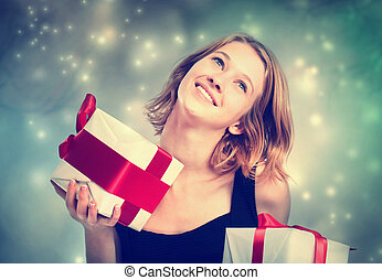 Happy young woman holding present boxes