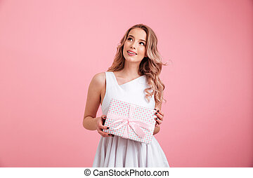 Happy young woman holding present gift box.