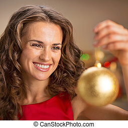 Happy young woman in red dress holding christmas ball