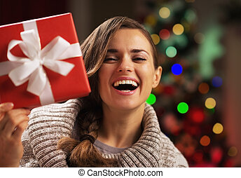 Happy young woman looking out from present box in front of christmas lights