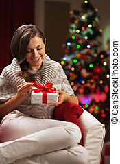 Happy young woman near christmas tree holding present box