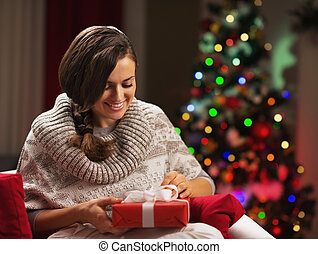 Happy young woman near christmas tree with present box