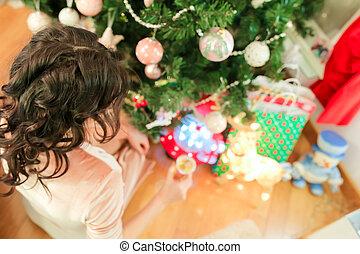 Happy young woman on Christmas eve near festive fir-tree
