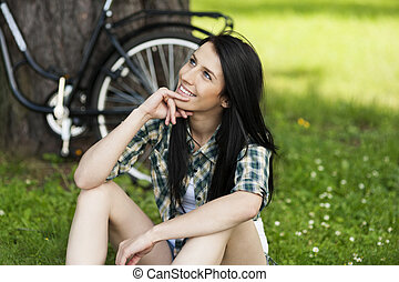 Happy young woman resting in park