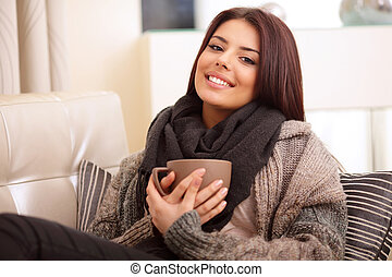 Happy young woman sitting on sofa in cosy cloths with cup of coffee