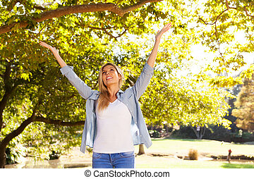 young woman with arms open under the trees
