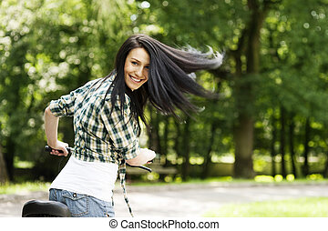 Happy young woman with bike in the park