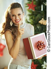 happy young woman with Christmas gift showing shh gesture