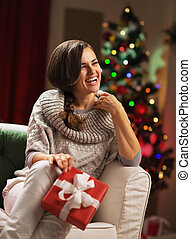 Happy young woman with christmas present box in front of Christmas