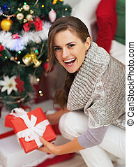 Happy young woman with christmas present box near christmas tree