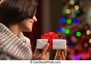 Happy young woman with present box in front of christmas lights