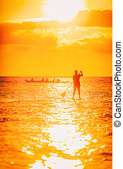Hawaii ocean lifestyle - watersport activity on ocean - stand up paddleboard, people training on outrigger canoe . Active summer healthy living. Silhouette of standing person doing paddle board