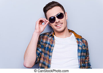 He is a real macho. Handsome young man in shirt adjusting his sunglasses and looking at camera while standing against grey background