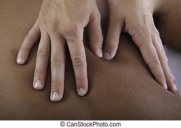 healing touch of a masseus's hands as she massages a young man