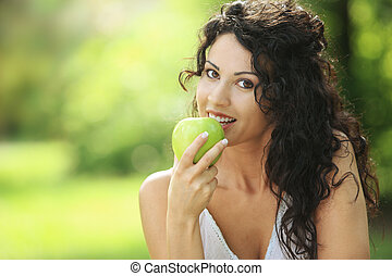 Beautiful cheerful woman eating a green apple, outdoors portrait