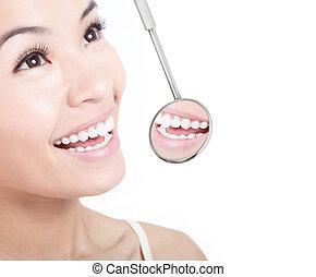 Healthy woman teeth and a dentist mouth mirror