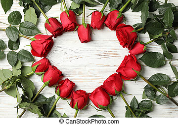 Heart of red roses on white wooden rustic background, top view