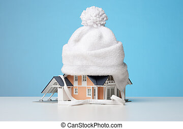 Baby cap isolate model of the house against heat leak - house insulation concept. Blue background.