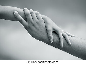 Man's and female hand on a background of the sky