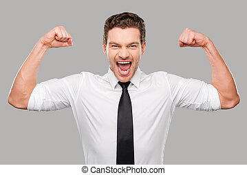 Hidden possibilities. Handsome young man in shirt and tie looking at camera and showing his biceps while standing against grey background