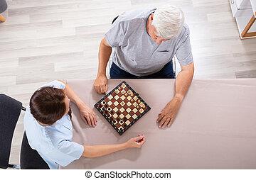 Caretaker Playing Chess With Senior Man On Desk