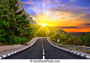 Highway against mountains and a dramatic sunset