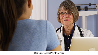 Hispanic patient talking to Senior doctor in office