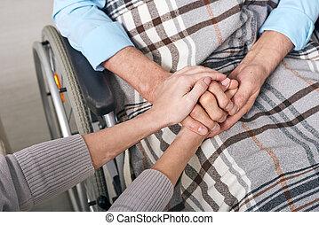 Holding hands of senior man