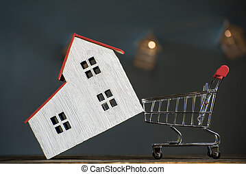 Home and shopping cart. Buying a house mortgage concept. Dark background, front view