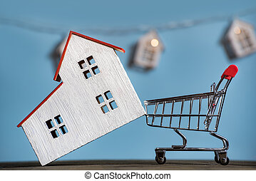 Home and shopping cart. Mortgage buying house concept. Blue background front view.