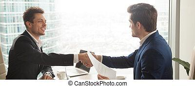 Horizontal image businessmen in suit handshaking sitting at modern office