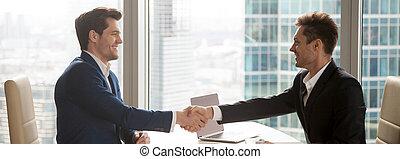 Horizontal image businessmen in suits handshaking sitting at office desk