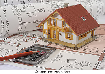 house building blueprint with financial calculator and red pencil