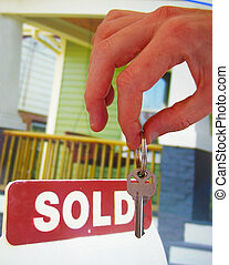 House for sale with sold sign and hand holding a key