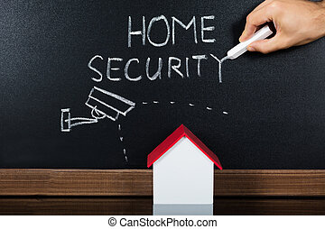House Model With Home Security Concept On Blackboard