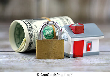 House, padlock and dollars. Conceptual image for investors in real estate and dollars. Security of money and real estate.