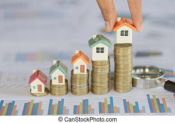 Human hand putting house model on coins stack. Concept for property ladder, mortgage and real estate investment