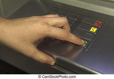 Human hand touching ATM machine