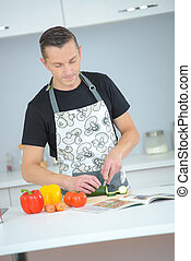 husband cooking dinner from recipe book