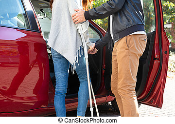 Husband Helping Her Disabled Wife To Get Inside The Car