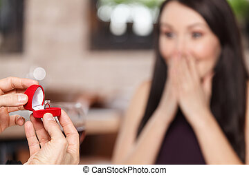 I do! Surprised women sitting with her hands covering mouth while her boyfriend holding an engage ring