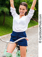 I love riding! Happy young woman riding her bicycle and keeping arms raised